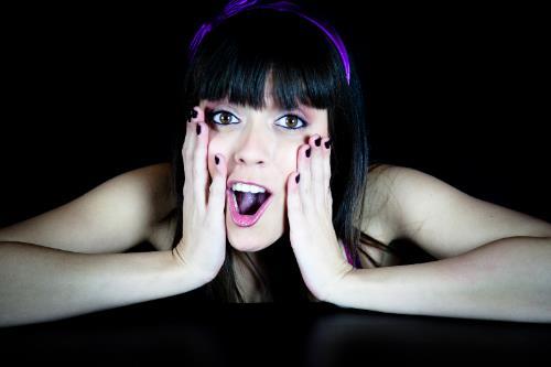 Chica en gesto de sorpresa con fondo negro